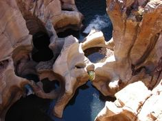 """Where the Blyde River (""""river of joy"""") and the Treur River (""""river of sorrow"""") meet, water erosion has formed one of the most remarkable geological phenomena: Bourke's Luck Potholes. Over thousands of years, surreal cylindrical rock sculptures created by whirling water, when the once rapid river carried masses of sand and debris, have formed a series of dark pools which contrast artfully with the streaked white and yellow lichen covered rocks."""