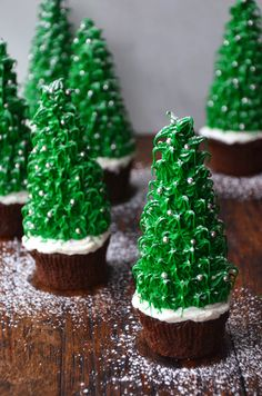 Christmas Tree Chocolate Cupcakes--Gingerbread houses, meet your match. These festive Christmas Tree Cupcakes serve a similar function as part dessert, part decoration for your holiday table. Moist chocolate cupcakes become the base of spruced up sugar cones adorned with bright green frosting and edible silver sprinkle ornaments and, the piece de resistance, a light dusting of powdered sugar snow.