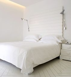 """""""A simple wood-slatted wall does double duty as a headboard."""" [Okay, but where'd that wood-slatted wall COME from??]"""