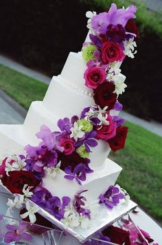 Love the cascading flowers. Purple, floral wedding cake.