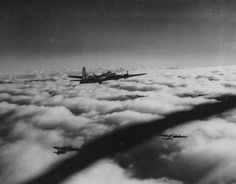 B-17 Flying fortress heavy bombers of the US Eighth Air Force in flight above the clouds over Nazi-occupied Europe.
