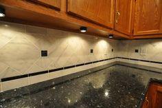 Emerald Pearl granite counter with Venetian White marble tile backsplash.