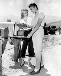 Full BTS shot of Anne Francis as Liz Wirth and John Ericson as Pete Wirth, opening mailbox, holding object