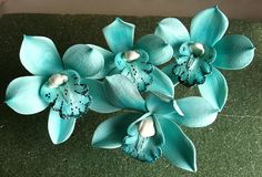 Gum paste flowers..... Cymbidium Orchids...great cake toppers.  Made out of gum paste and edible food dye..the color of these are teal with a white center and the throat/lip of the orchid is hand painted as well.  If you are making your own wedding cake or having someone do it for you, these would great on your cake.