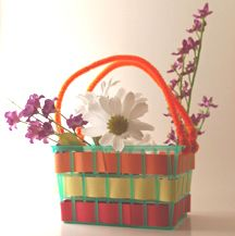may basket idea How You Make It: Cut strips of construction paper slightly narrower than the spaces in the strawberry basket. Weave paper strips in and out, overlapping at ends to secure. Twist ends of pipe cleaner at top of one side of berry basket. Repeat on opposite side. Fill with real or fake flowers or use for Baby Moses.