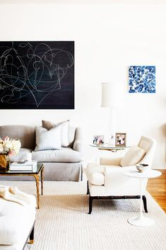 Light and bright living room with gray couch and modern art.