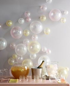 Tape balloons in all sizes to the wall. Perfect for a celebration or New Year's Eve party. Bubbles that never go flat.