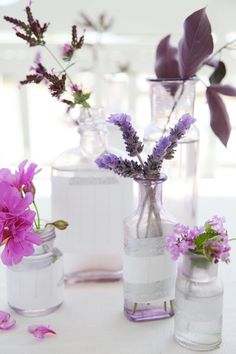 Floral centrepiece of purple lavender and pink flowers in frosted glass vases.
