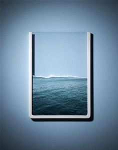 It's a picture of the ocean that's ripped on top, and placed in a frame with the top part of the frame removed to make it look almost like it's holding the water. clever