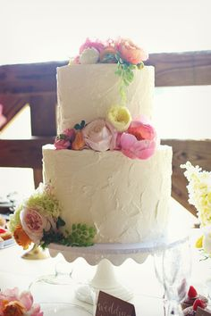 Two tiered cake with flowers add swiss dots around the bottom of each tier