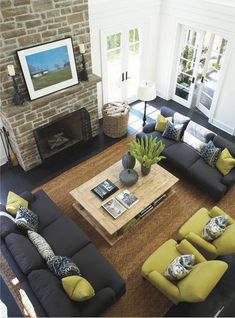 Pretty living room - charcoal couches & green accents. White walls + white trim (maybe could do black or dark on interior of windows?) dark wood floors with natural accents in rug & fireplace.