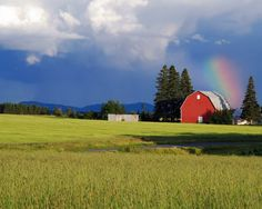 A brilliantly colored rainbow overlooking a barn in Aroostook County, Maine.