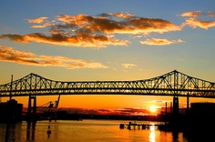 """MYSTIC RIVER SUNSET  If you saw the movie directed by Clint Eastwood, or read the book by Dennis Lehane... this is the spot where Tim Robbins character, Dave Boyle, gets it in the end. This bridge connects Chelsea to Boston over the Mystic River. Originally called the Mystic River Bridge, in 1967, it was renamed """"Tobin Bridge"""" in honor of Maurice J. Tobin, former Boston mayor and Massachusetts governor. Copyright 2005 by Rick Macomber"""