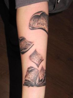 Book tattoo with loose pages. To tie my upper arm tattoo (fields of flowers)with the lower (tea and books) to form a full sleeve. Daisies and pages swirl together with color shift behind