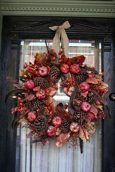 lovely wreath using a combination of feathers, berries, pine cones, and pomegranates.