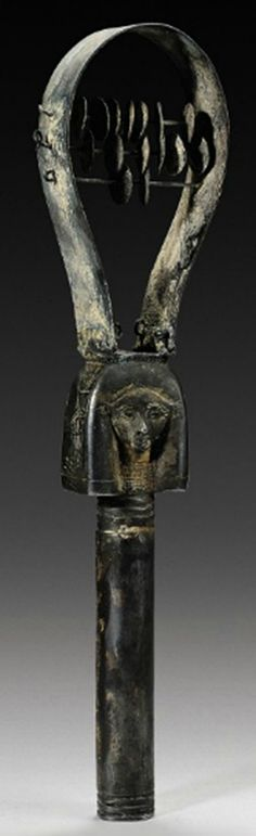 An ancient Egyptian silver sistrum in the form of the janiform head of the goddess Hathor, with cow ears, each side of the wig incised with a uraeus, one wearing crown of Upper Egypt, the other wearing crown of Lower Egypt. (Christie's)