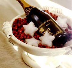 Champagne bottle chilled in urn full of frozen cranberries and star-shaped ice cubes.