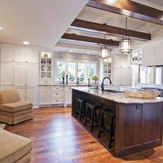 White trim, white cabinets, dark island, beams and wood floors