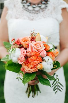 Peach roses and cotton are in this bridal bouquet