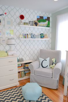 This stencil wall is a great backdrop for frames and books in a #white #nursery. #stencilwall