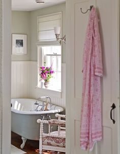 The master bath features a claw-foot tub that came with the house and a white-painted 19th-century English spool chair with an upholstered seat and arms.    Read more: Colonial Farmhouse Decor - Rhode Island Farmhouse Tour - Country Living