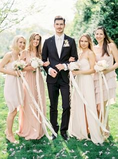 long strands of ribbon tied to the bridesmaids bouquets   repin via: one fab day