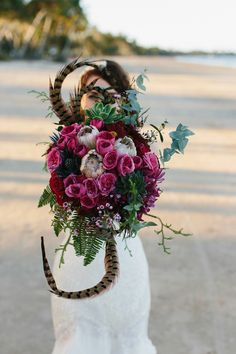 tropical bouquet with feathers, photo by David Campbell Imagery http://ruffledblog.com/elandra-resort-wedding #weddingbouquet #flowers