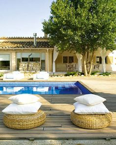 natural whites with tile roof; IKEA ottomans; deck around the pool; from style files