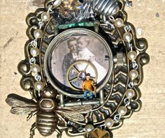 http://www.etsy.com/listing/73956283/antique-jewelry-brooch-or-necklace-bees       ingredients :    original antique photograph of children-sweethearts  little vintage train man sitting in watch case. He's a tiny little figure used for train displays-love them!  vintage watch parts, gear, crystal, watch case  vintage brass flower stamping-about 1940's  rosary chain  large antiqued bronze ornate plate base.  two bees, one antiqued bronze, the other silver ox  vintage chandelier crystal at the top by the...