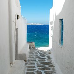 Mykonos, Greece. Vacation destination! Complete with the white and blue buildings, complementing the sea, sky, and dotty white waves.