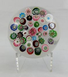 Clichy concentric circle millefiori glass paperweight, with a central pink and green cabbage rose cane and one pink and white cabbage rose cane in the outermost ring, ca. 1850. $2,500.00 millefiori glass, rose cane
