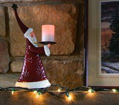 Cheery vintage-style metal Santa and its accompanying flameless candle.
