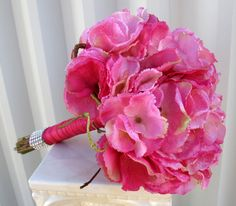 Wedding bouquet of vibrant hot pink hydrangea, framed with curly willow. Handle treatment is wrapped with satin ribbon and a shear hot pink overlay ribbon, crystal rhinstone wrap on base of handle to finish.