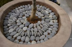Use river rock to make a decorative pebble mosaic pattern in a planter