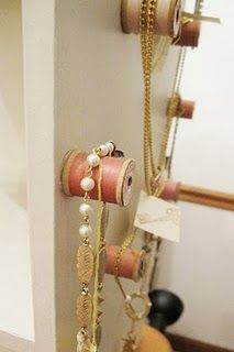 Vintage cotton reels attached to an upright board by Good Girls Studio are perfect for hanging necklaces from.
