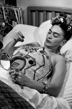 Frida Kahlo in bed recuperating, drawing on her corset with help of a mirror, 1951.