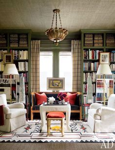 Interior designer J. Randall Powers fashioned a chic leaf-green library for the Houston home he shares with investor William L. Caudell. A Biedermeier settee accompanies a John Dickinson plaster table, while a Navajo-inspired rug tops a sisal floor covering.