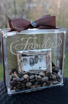 Clear glass block with family picture inside. Get the blocks that open at Michaels.  Place wedding sand in block.