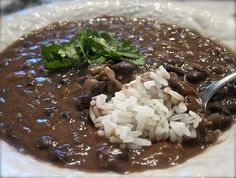 Easy Black Bean Soup 2 cans of seasoned black beans (drained, not rinsed) 1 can chicken broth 1 1/2 cups water 2 Tbsp olive oil 1 cup chopped onion 2 cloves of garlic minced 2 tsp chili powder 1/4 tsp cumin White Rice (use brown rice)