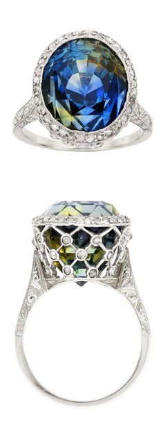 Edwardian Chameleon Sapphire, Diamond, Platinum, Gold Ring  The ring features an oval-shaped chameleon sapphire  weighing approximately 15.70 carats, accented by rose-cut diamonds  set in platinum, completed by an engraved 18k white gold shank