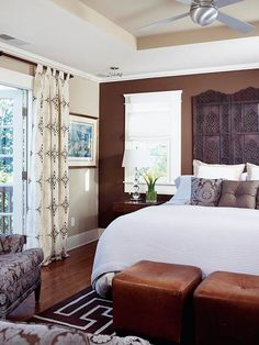 Chocolate Brown  Apply the same color to different TEXTURES in the room.  A smooth accent wall, carved wood headboard, leather ottomans, and graphic rug all are the same rich color...which add dimension, luxury to the room.  Note the lighter shades of tan in the cove ceiling and pretty drapes.
