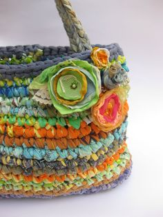 This big purse / mini tote is hand crocheted from so many different kind of fabrics and plastic bags yarn (or plarn).    by Osnat Ganors