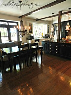 Husband & wife team makeover their dated kitchen with black & white paint, wood beams made out of wood from Home Depot, x moldings stuck in windows, copper knobs which were originally bronze (she sanded them down), and new light fixtures.  #kitchenmakeover #blackcabinets #woodbeams #amazingkitchen