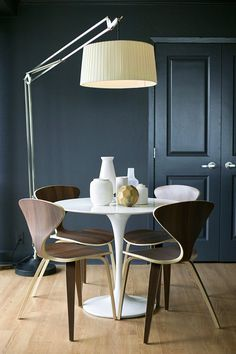 Modern dining room with black walls and oversized lamp.