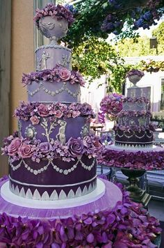 Silver Grecian details, rings of impeccably crafted sugar flowers and a dramatic bowl of flowers on top cover this purple ombré cake.