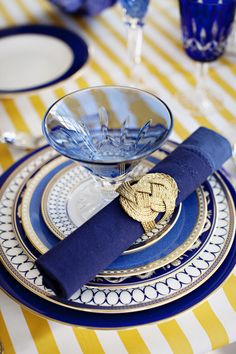 bright yellow and white striped cloth with cobalt dishes and glasses