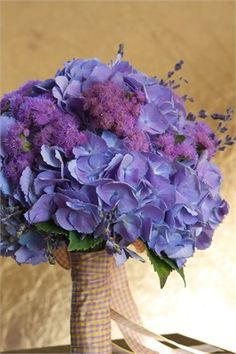 A purple bouquet tied with gingham ribbon to add a country feel to any wedding day.
