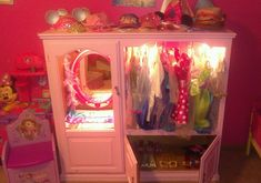 My husband and I made this for our daughters out of an old entertainment center :)  We took the glass window out, added a $25 Disney Princess mirror from Walmart that lights up and talks when you push the button on it. Then we used a $3 tension rod to hang the dress-up dresses on.  We painted it with a pretty pink mixture he made and it took 3 coats.  Then, he used small lights inside of it for added effect.  Very cheap  easy to make and out little girls LOVE it!