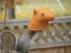 a squirrel eating from the squirrel-head-shaped squirrel feeder