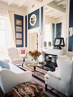 Preppy Navy Blue    Blue is traditionally used to highlight architectural details. Painted panels topped by crisp white molding and gilded frames give this living room an ultra-preppy personality. Photography by Patrick Cline for Lonny Magazine